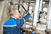 image of plumber  - repairman plumber engineer of fire engineering system or heating system open the valve equipment in a boiler house - JPG