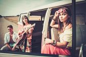 image of hippy  - Young hippie friends with guitar on a road trip - JPG