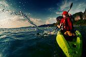 stock photo of kayak  - Young lady paddling hard the sea kayak with lots of splashes - JPG