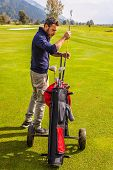 picture of golf bag  - a golf player playing on a beautiful golf course and a golf bag full of golf clubs - JPG