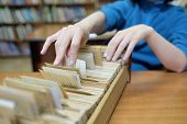 foto of librarian  - Librarian woman searches something in card catalog - JPG