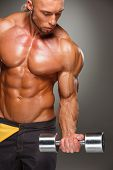 stock photo of body builder  - Attractive male body builder with dumbbell on gray background - JPG