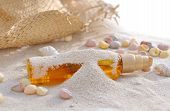 pic of suntanning  - bottle of suntan oil covered by sand with shells and cap - JPG
