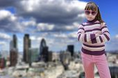 pic of blown-up  - Teenage girl in pink wears sunglasses modern city in background - JPG
