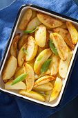 pic of baked potato  - baked potato wedges in enamel baking dish - JPG