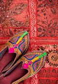 picture of flea  - Colorful ethnic shoes on red Rajasthan cushion cover on flea market in India - JPG