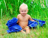 picture of naked children  - Little child sitting on the grass with blue towel - JPG