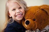 image of preschool  - Portrait of an adorable preschool age girl playing with a teddy bear - JPG