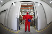 stock photo of supply chain  - A fish eye view of a worker standing in the doorway of a modern industrial facility - JPG