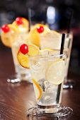 stock photo of collins  - Four Tom Collins cocktails shot on a bar counter - JPG