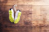 stock photo of wooden fence  - Pair of sneakers hang on a nail on a wooden fence background - JPG