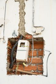 foto of electricity meter  - Unfinished wiring and electricity meter on a wall - JPG