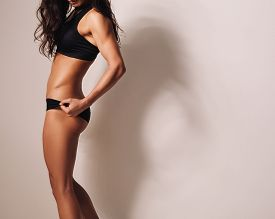 stock photo of slim model  - Mid section image of strong young woman in sportswear posing against wall - JPG