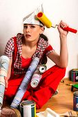 Repair home woman holding paint roller for wallpaper. Tired and frustrated female in newspaper cap r poster