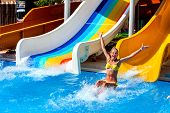 Swimming pool slides for child on blue water slide at aquapark . Summer kids ride holiday outdoor. H poster