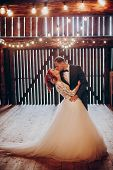 Stylish Groom And Happy Bride Kissing Under Retro Bulbs Lights In Wooden Barn. Rustic Wedding Concep poster
