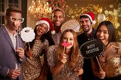 Group Of Friends Dressing Up For Christmas Party Together poster