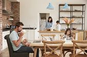Busy Family Home With Father Working As Mother Prepares Meal poster