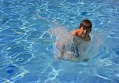 A Young Boy Jumping And Splashing Into A Swimming Pool