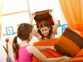 foto of pillow-fight  - Happy schoolgirls in pillow fight in living room - JPG