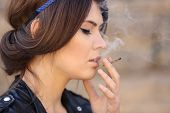 Beautiful young woman smoking weed outdoors poster