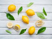 Fresh Lemons And  Lemons Leaves On Rustic Wooden Background. Fresh Lemons And Lemon Slice On Wooden poster