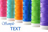 Colorful spools of thread on white background with copy space.  Macro with shallow dof.  Selective f