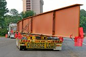 stock photo of oversize load  - A giant steel beam for a highway bridge on a truck - JPG
