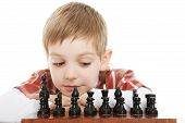 boy looking on chess