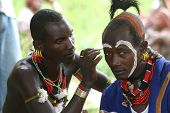 Hamer tribesmen of Ethiopia, paint their faces before a wedding