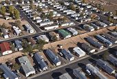 Aerial of aging mobile homes in bright desert sun.