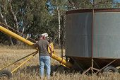 image of auger  - farm worker checking auger motor before starting - JPG
