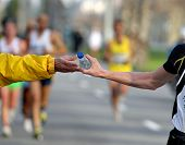 Runner take a bottle of water in a long distance race