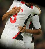 Male Soccer players in white t-shirt standing hugging united and showing team spirit in a game on th