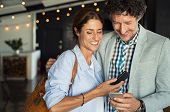 Smiling mature couple embracing while looking at smartphone. Couple sharing media on smart phones wh poster