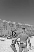 Young Sporty Active Couple Stand Near Volleyball Net Play Game On Summer Day. Couple Have Fun Playin poster