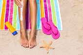 Sunscreen woman applying sun tan cream sunblock lotion on legs with bottle, flip flops and sea star  poster