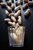 Still Life With Dried Peanuts In Their Nutshells And Small Vintage Glass Against A Low Key Backgroun poster