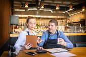Young Man And Woman Going Through Paperwork Together In Their Restaurant. Small Family Restaurant Ow poster