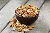 Wooden Bowl With Mixed Nuts On A Wooden Gray Background. Walnut, Pistachios, Almonds, Hazelnuts And poster