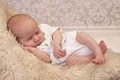 foto of newborn baby  - Tired newborn baby fast asleep on a fur blanket and vintage wallpaper - JPG