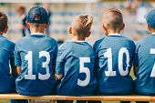 Boys Sitting On Soccer Football Wooden Bench. Kids Football Team. Soccer Tournament Match For Childr poster