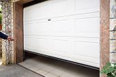 Garage Door Pvc. Hand Use Remote Controller For Closing And Opening Garage Door poster