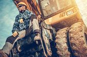 Caucasian Excavator Operator Sitting On His Excavator. Heavy Duty Ground Working Machinery. Construc poster