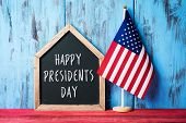 an american flag and a house-shaped chalkboard with the text presidents day written in it on a red w poster
