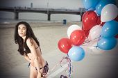 stock photo of string bikini  - Beautiful model wearing the United States flag bikini on skates holding USA color ballons at the beach sidewalk - JPG