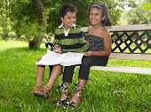 Asian Kids Reading A Book In A Park