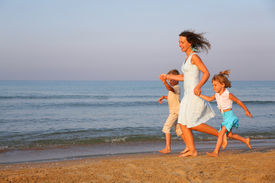 stock photo of mother child  - Mother with children running on edge of sea - JPG
