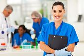 attractive young female lab technician in lab with colleagues