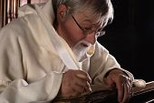 Monk writing in an ancient book with a feather quill